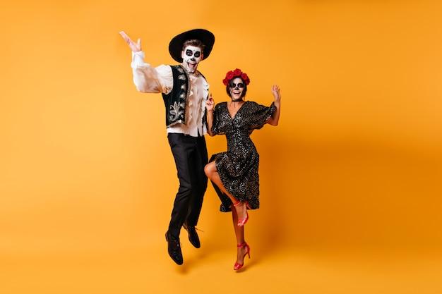 Радостный человек-зомби в сомбреро прыгает на желтой стене. очаровательная девушка muerte в черном платье танцует с парнем.