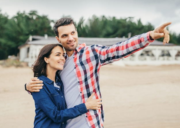 Gladful family couple have excursion in city, hug each other, look into distance as see somethning admirable, have good relationships. spending free time outdoor. people and leisure concept.