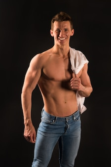 Гладиатор или атлант. спорт и тренировки. человек с мускулистым телом. парень с обнаженной грудью в джинсах и рубашке. атлетическая поза культуриста.