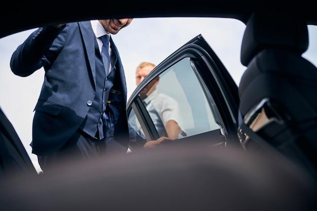 出張に行く車の中に入る派手なスーツを着ているうれしいブルネットの男