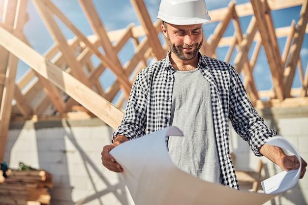 紙の上の建築計画を見てうれしいエンジニア
