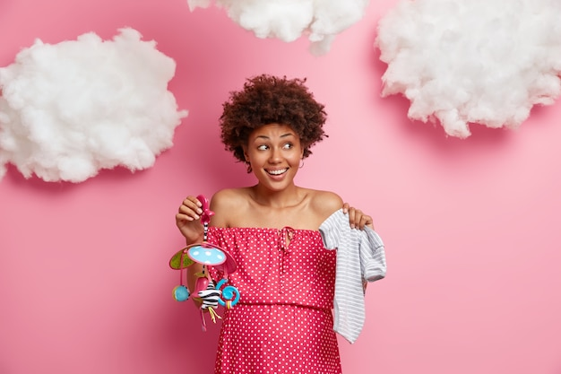 Gladsome ethnic woman poses with baby bodysuit and mobile, will become mother soon, looks happily aside, has big belly, wears polka dot dress, isolated on pink wall, white clouds overhead