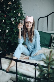 Радостная молодая дама в маске для глаз и пижаме радуется со стеклом, сидя в постели с елкой