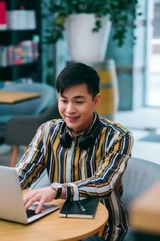 Радостный молодой человек сидит за столом с современным ноутбуком и улыбается, используя его