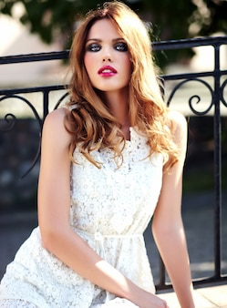 Glamor beauty portrait of beautiful sensual caucasian young woman model with evening makeup in white summer dress posing on the street background