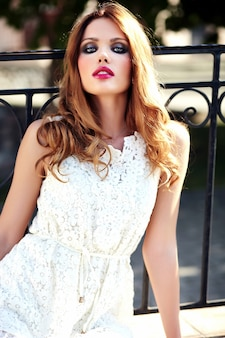 Glamor beauty portrait of beautiful sensual caucasian young woman model with evening makeup in white summer dress posing on the street