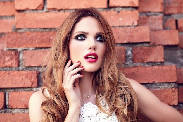 レンガの壁の近くの通りの背景にポーズをとって白い夏ドレスで夜のメイクと美しい官能的な白人の若い女性モデルの容姿の美しさの肖像画