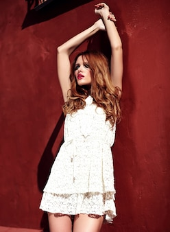 赤い壁の近くの通りの背景にポーズをとって白い夏のドレスで夜のメイクと美しい官能的な白人の若い女性モデルの容姿の美しさの肖像画