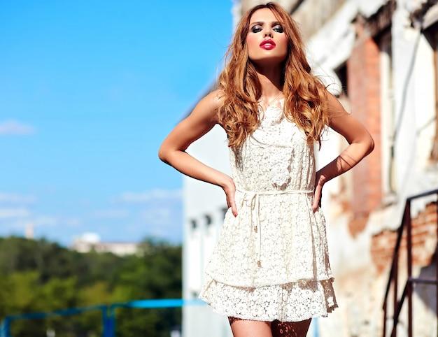 通りの背景にポーズをとって白い夏ドレスで夜メイクで美しい官能的な白人の若い女性モデルのグラマー美容肖像画