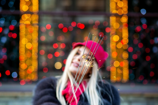 Glamor blonde woman having fun with sparklers against garlands blurred background