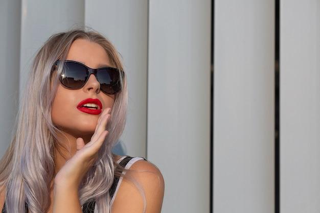 Гламурная блондинка с красными губами в солнцезащитных очках позирует возле жалюзи. место для текста