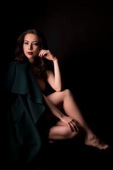 スタジオで影の暖かいコートを着た魅力的なブルネットの女性