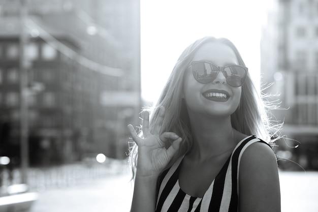 夏の日を楽しんで、okジェスチャーを示すメガネのグラマー陽気なモデル。空きスペース。黒と白の調子を整える