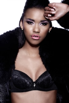 Glamor closeup portrait of beautiful sexy black young woman model with bright makeup  with perfect clean in fur coat