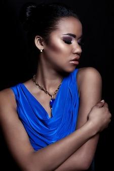 完璧なきれいな肌と明るいメイクとアクセサリーと青いドレスの美しいセクシーな黒若いスタイリッシュな女性モデルの容姿のクローズアップの肖像画
