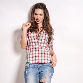 Glamor stylish beautiful young woman model with red lips in summer bright colorful jeans