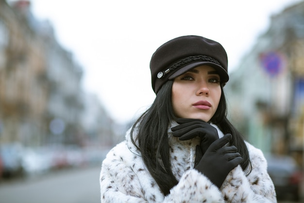 冬に屋外でポーズをとるキャップと毛皮のコートを着ている魅力的な若いモデル。空きスペース
