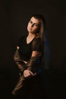 스튜디오에서 포즈를 취하는 갈색 가죽 재킷에 예술 화장을 한 매력적인 젊은 여성