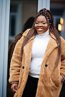 暖かい毛皮のコートを着た魅力的なアフリカ系アメリカ人の女性、眼鏡が通りでポーズをとる。