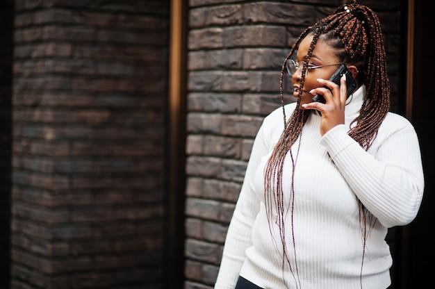 흰색 터틀넥 스웨터에 매력적인 아프리카 계 미국인 여자는 휴대 전화와 함께 거리에서 포즈.