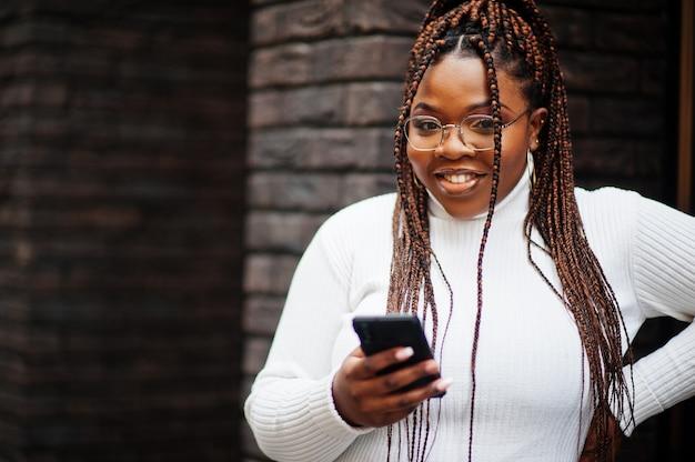 白いタートルネックのセーターを着た華やかなアフリカ系アメリカ人女性が携帯電話で通りにポーズをとる。