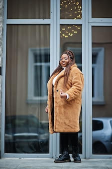 Glamorous african american woman in warm fur coat, eyeglasses pose at street.