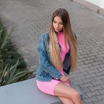 매력적인 매력적인 젊은 여자 유행 데님 재킷에 세련된 핑크 탑에 빈티지 핑크 반바지에 긴 머리를 가진 금발은 녹색 식물 근처에 앉아 야외에서 이완합니다. 귀여운 소녀. 레트로 스타일.