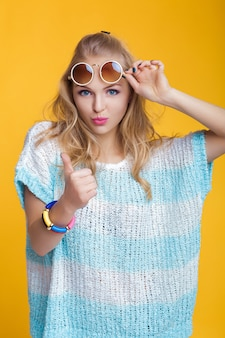 Glamorous beautiful blond woman in sunglasses and blue shirt giving thumbs up on yellow background h...