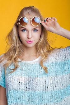 Glamorous beautiful blond woman in sunglasses and blue shirt on yellow background happy summer time