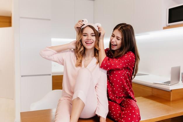 주말 아침 식사 전에 여동생과 함께 장난하는 매력적인 갈색 머리 소녀. 잠옷에 두 웃는 화려한 숙녀의 실내 사진.