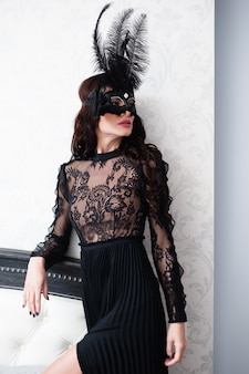 Glamorous brunette lady with a beautiful hairstyle and red lips, in an evening dress, a venetian black mask with stylish accessories