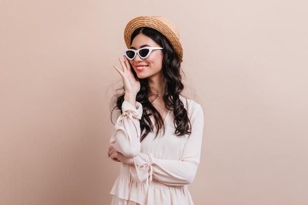 ベージュの背景で笑っている魅力的なブルネットの女性。麦わら帽子をかぶった至福の若い女性のスタジオショット。