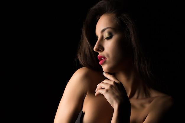 影でポーズをとって裸の肩を持つ明るい化粧の魅力的なブルネットの若い女性
