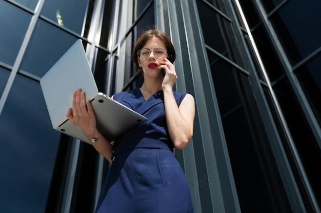 ビジネスセンター近くのラップトップで電話で話している美しいスーツで赤い唇を持つ華やかなビジネス女性