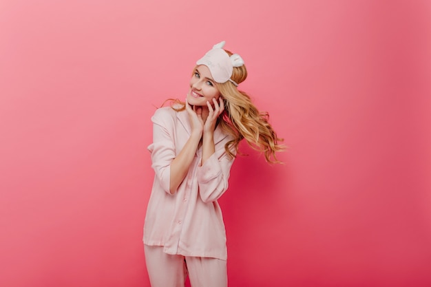 Гламурная кудрявая девушка, выражающая энергию по утрам. приятная кавказская женщина в шелковой пижаме позирует на розовой стене.
