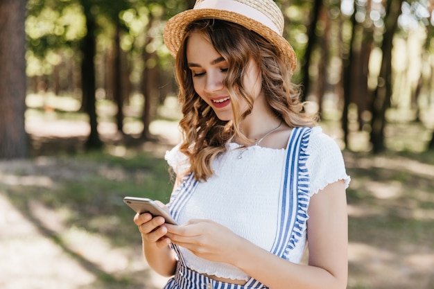 電話の画面を見ている流行の服を着た魅力的な巻き毛の女の子。公園での写真撮影後の帽子のテキストメッセージメッセージで魅力的な女性モデルの屋外ショット。