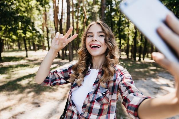 숲에서 미소로 포즈를 취하는 매력적인 곱슬 소녀. 자연에 셀카를 위해 스마트 폰을 사용하는 매력적인 여성 모델.