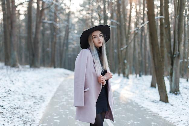 우아한 모자에 세련 된 따뜻한 매력적인 옷에 매력적인 귀여운 아름 다운 젊은 여자는 겨울 맑은 날에 눈 덮인 공원에서 도로에 선다. 유행 매력적인 현대 소녀.