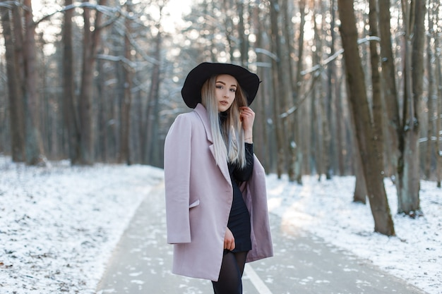 Glamorous cute young woman blonde in an elegant stylish hat in a knitted golf in a skirt in a fashionable pink coat posing standing on a track in a snowy park on a warm winter sunny day. nice girl.
