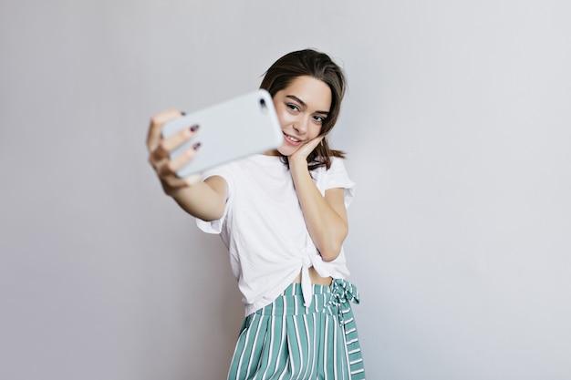 スマートフォンを自分撮りに使っているグラマラスな黒い瞳の女の子。自分の写真を撮るブルネットの愛らしい女性。