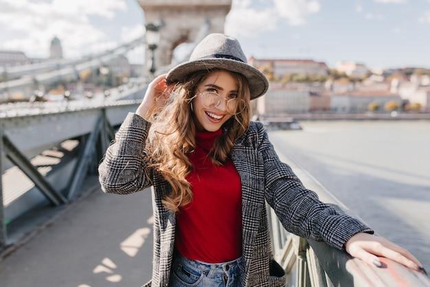 Affascinante ragazza europea in maglione rosso trascorrere il tempo libero all'aperto nella soleggiata giornata autunnale