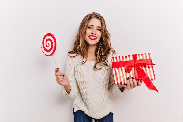 새 해 선물을 들고 웃 고 세련 된 스웨터에 매력적인 유럽 여자. 롤리팝과 리본으로 장식 된 상자와 함께 포즈 곱슬 소녀의 실내 초상화.