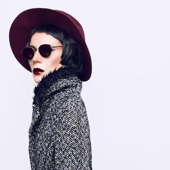 スタイリッシュなコートと帽子の華やかなファッションの女性。ビンテージ・スタイル