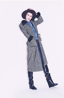 コートとスタイリッシュなジーンズの服で華やかなファッションモデル。