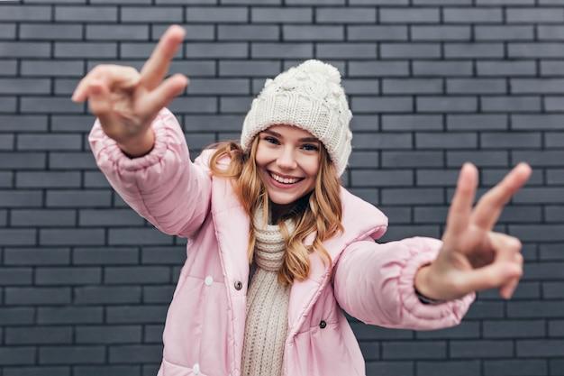Modello femminile affascinante in giacca invernale rosa in posa con il segno di pace. colpo esterno di ridere allegra donna bionda in cappello lavorato a maglia.