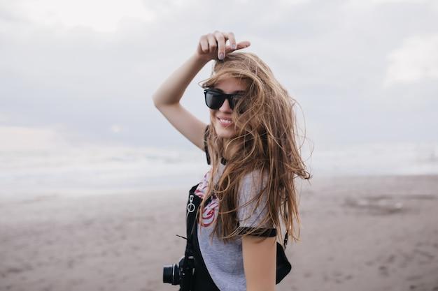 바람이 부는 날에 웃 고 매력적인 여성 사진 작가입니다. 카메라와 함께 해변에서 포즈를 취하는 동안 행복을 표현하는 세련 된 재미있는 여자의 야외 촬영.