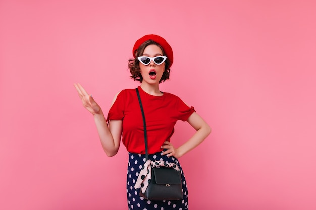 빨간 t- 셔츠 포즈에 매력적인 프랑스 여자입니다. 베레모와 선글라스에 갈색 머리 유럽 여자의 실내 사진.