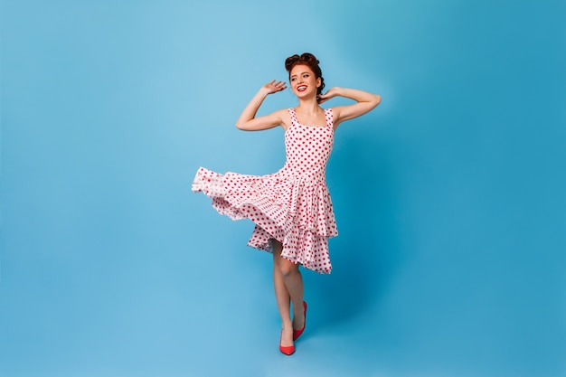 푸른 공간에 춤을 매력적인 생강 소녀. 폴카 도트 드레스에 멋진 핀업 여자의 스튜디오 샷.