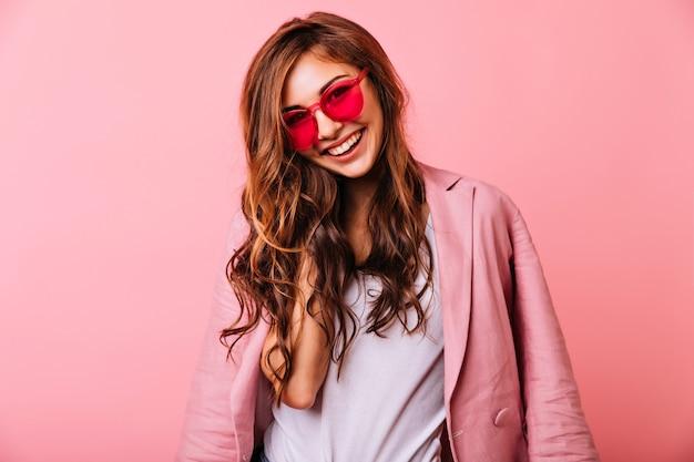 ポジティブな感情を表現するピンクのメガネの華やかな生姜の女の子。肖像画を楽しんで幸せな若い女性。