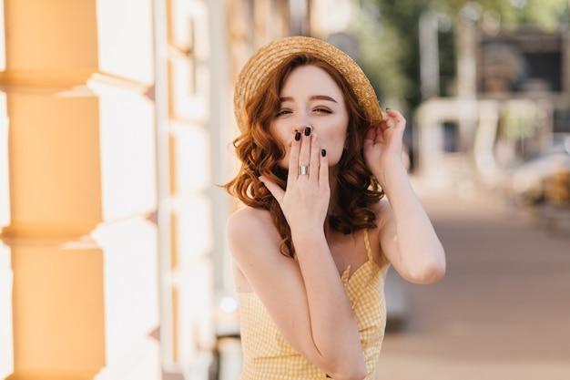 Affascinante ragazza dello zenzero in abito giallo che manda un bacio d'aria durante il servizio fotografico estivo. colpo esterno di giocosa donna dai capelli rossi in cappello di paglia che esprime amore.